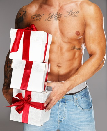 Man with tattooed muscular torso with gift boxes photo