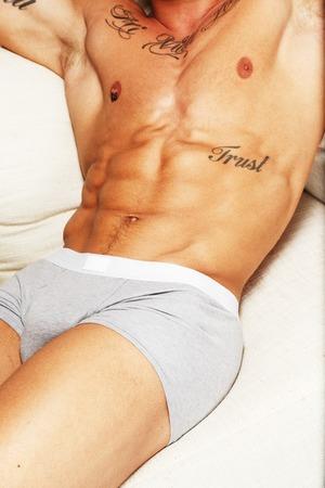 Man with beautiful muscular tattooed torso in underwear lying on sofa photo