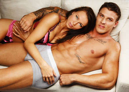 nude woman sex: Young beautiful sexy couple in underwear lying on sofa