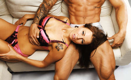 Young beautiful sexy couple in underwear lying on sofa photo