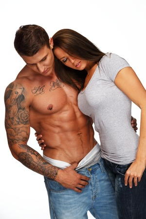 Young woman embracing man with naked muscular torso  photo