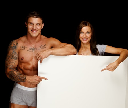 Man with muscular tattooed torso and woman holding blank notice board photo
