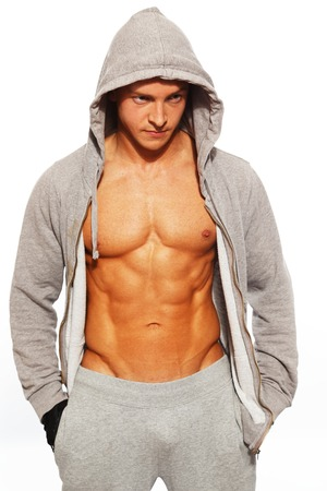 Handsome man in grey hoodie showing his abdominal muscles photo