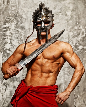 Gladiator with muscular body with sword and helmet photo