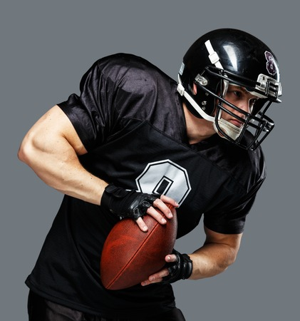 american football helmet: American football player with ball wearing helmet and jersey