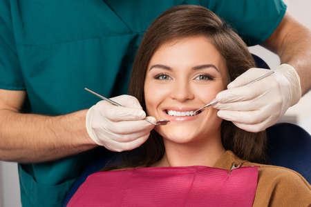 mooie brunette: Jonge mooie brunette vrouw in de spreekkamer tandarts Stockfoto