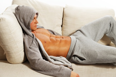 Sporty man in grey hoodie with muscular torso relaxing on sofa photo