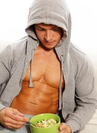 アスリート: 新鮮なサラダを食べて筋肉胴とグレーのパーカーでスポーティな男