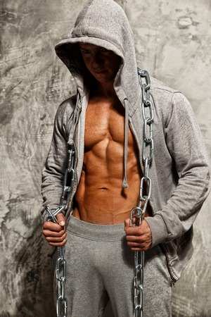 Sporty muscular man in grey hoodie with heavy metal chain photo