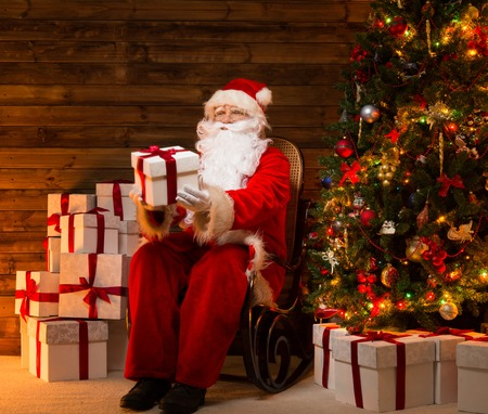 Santa Claus sitting on rocking chair in wooden home interior presenting gift box photo