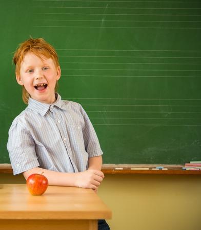grade schooler: Little funny redhead schoolboy near blackboard with apple on a table  Stock Photo