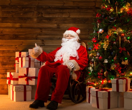 Santa Claus sitting on rocking chair with thumb up in wooden home interior with gift boxes around him  photo