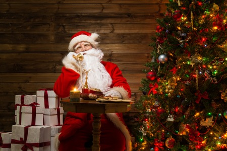 Santa Claus  with phone in wooden home interior  photo