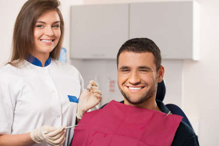 Happy male patient and smiling female dentist at dental surgery photo