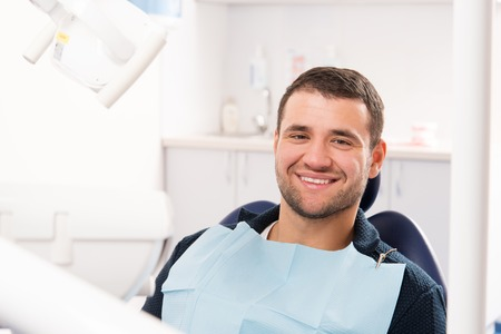dentists surgery: Smiling young man at dentists surgery