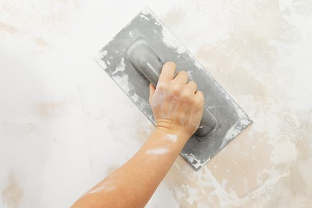 putty: Process of levelling off crack filler on a wall