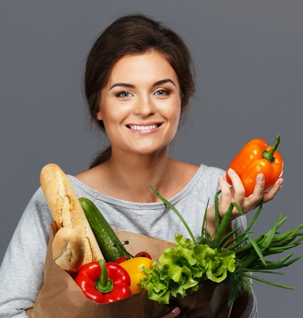Smiling young brunette woman with grocery bag full of fresh vegetables photo