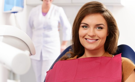 Young brunette woman with beautiful smile visiting dentist  photo