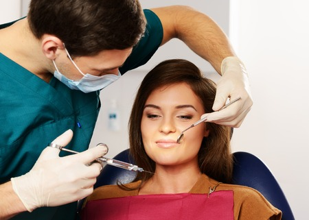 anaesthetic: Dentist making anaesthetic injection to woman patient