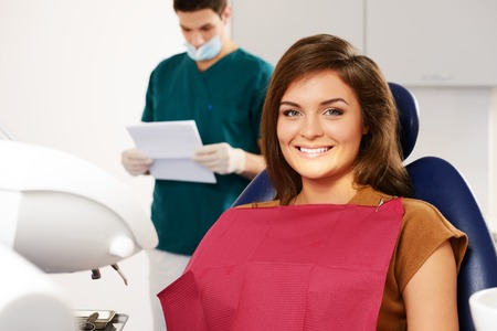 Man dentist reading woman patient's card Stock Photo - 24718441