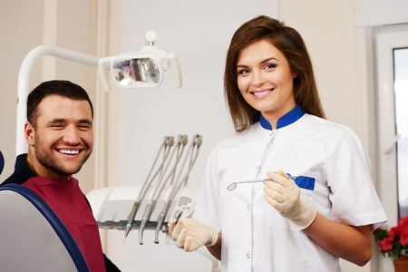 Happy man patient and smiling woman dentist at dental surgery photo