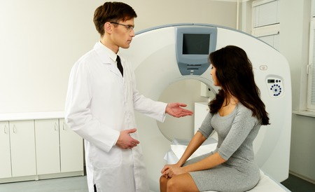 computer tomography: Young doctor talking to woman patient at computed tomography lab Stock Photo