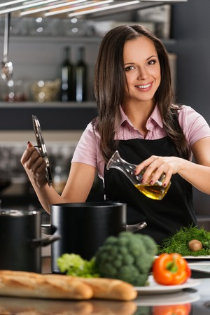 young add: Smiling young woman adding oil to pot on a modern kitchen