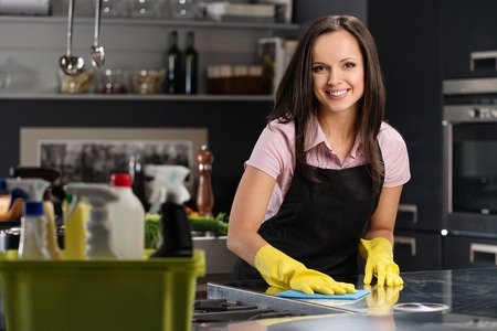 cleaning: Beautiful cheerful brunette woman in gloves cleaning modern kitchen Stock Photo