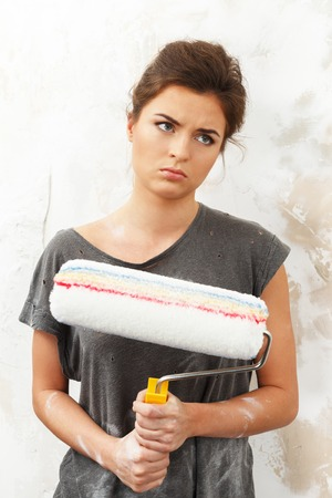 housepainter: Disgruntled young brunette woman doing wall painting