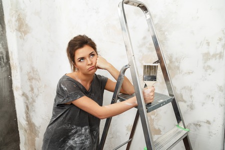 disgruntled: Disgruntled young brunette woman with ladder and painting brush Stock Photo