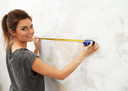 spacing: Young beautiful brunette woman measuring spacing on a wall with roulette