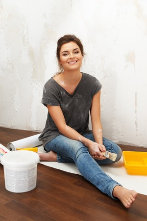 housepainter: Happy beautiful young woman doing wall painting
