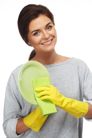 dish washing: Beautiful cheerful brunette woman in gloves cleaning plate