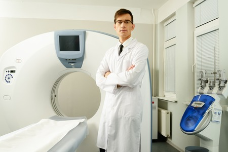 computer tomography: Young doctor standing near computed tomography scanner in a hospital Stock Photo