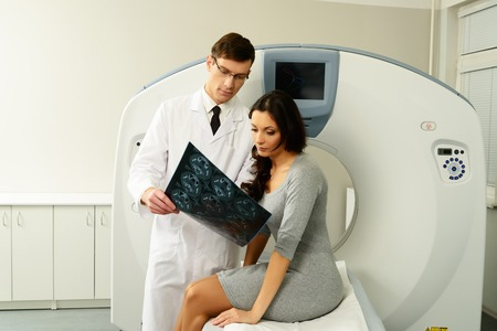 computer tomography: Doctor with young woman patient looking at the computed tomography results