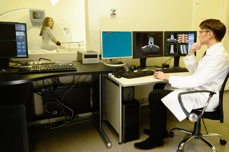computer tomography: Young doctor sitting behind monitors in a computed tomography laboratory