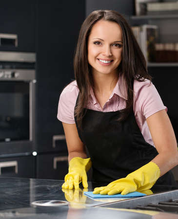 charwoman: Beautiful cheerful brunette woman in gloves cleaning modern kitchen Stock Photo
