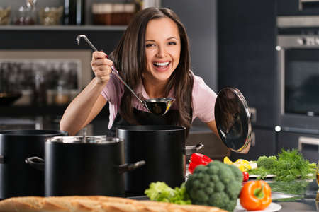 vegetable cook: Cheerful young woman in apron on modern kitchen will ladle tasting from pot