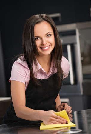 charlady: Beautiful cheerful brunette woman  cleaning modern kitchen