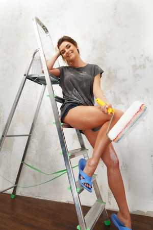 Happy beautiful young woman doing wall painting photo