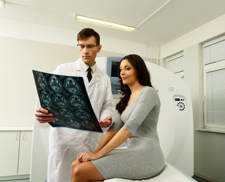 Doctor with young woman patient looking at the computed tomography results photo