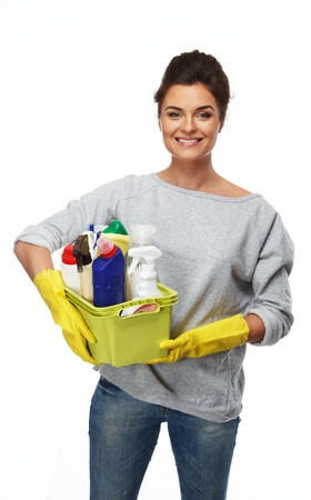 charlady: Beautiful cheerful brunette woman in gloves holding different cleaning stuff