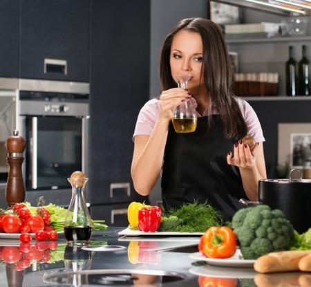 aceite de cocina: Mujer joven con delantal en la cocina huele el aceite de oliva moderna
