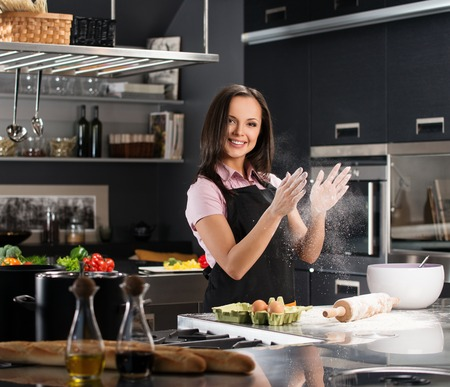 goods: Young woman having fun with flour while making dough on a modern kitchen