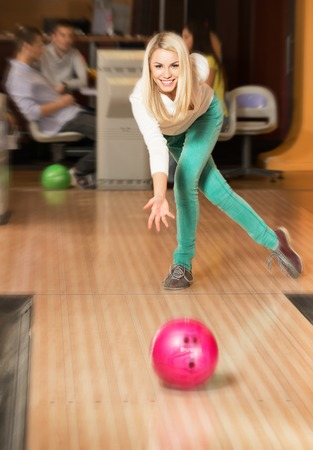 Young smiling blond woman throwing ball in a bowling club photo