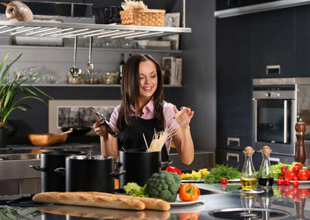 Smiling young woman cooking spaghetti on a modern kitchen  photo