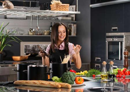 Sonriendo jóvenes espaguetis Cocinar a la mujer en una cocina moderna Foto de archivo