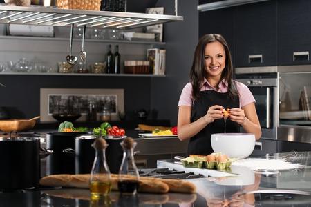 Mujer joven en el delantal de romper los huevos para una pasta en una cocina moderna