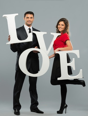 Beautiful smiling couple holding word LOVE made from foam plastic photo