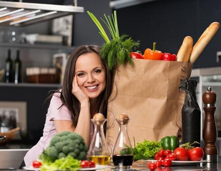 bolsa de pan: Mujer joven con una bolsa de supermercado llena de verduras frescas en una cocina moderna